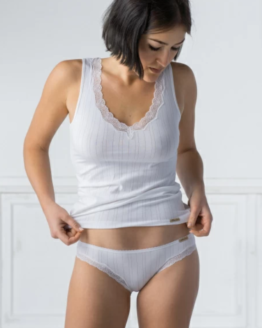 Model met wit onderhemd met kant en streepjes en wit ondergoed beide van comazo